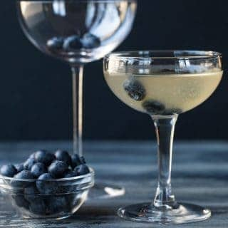 Blueberry Martini is a coupe glass with blueberry floating in it for garnish.