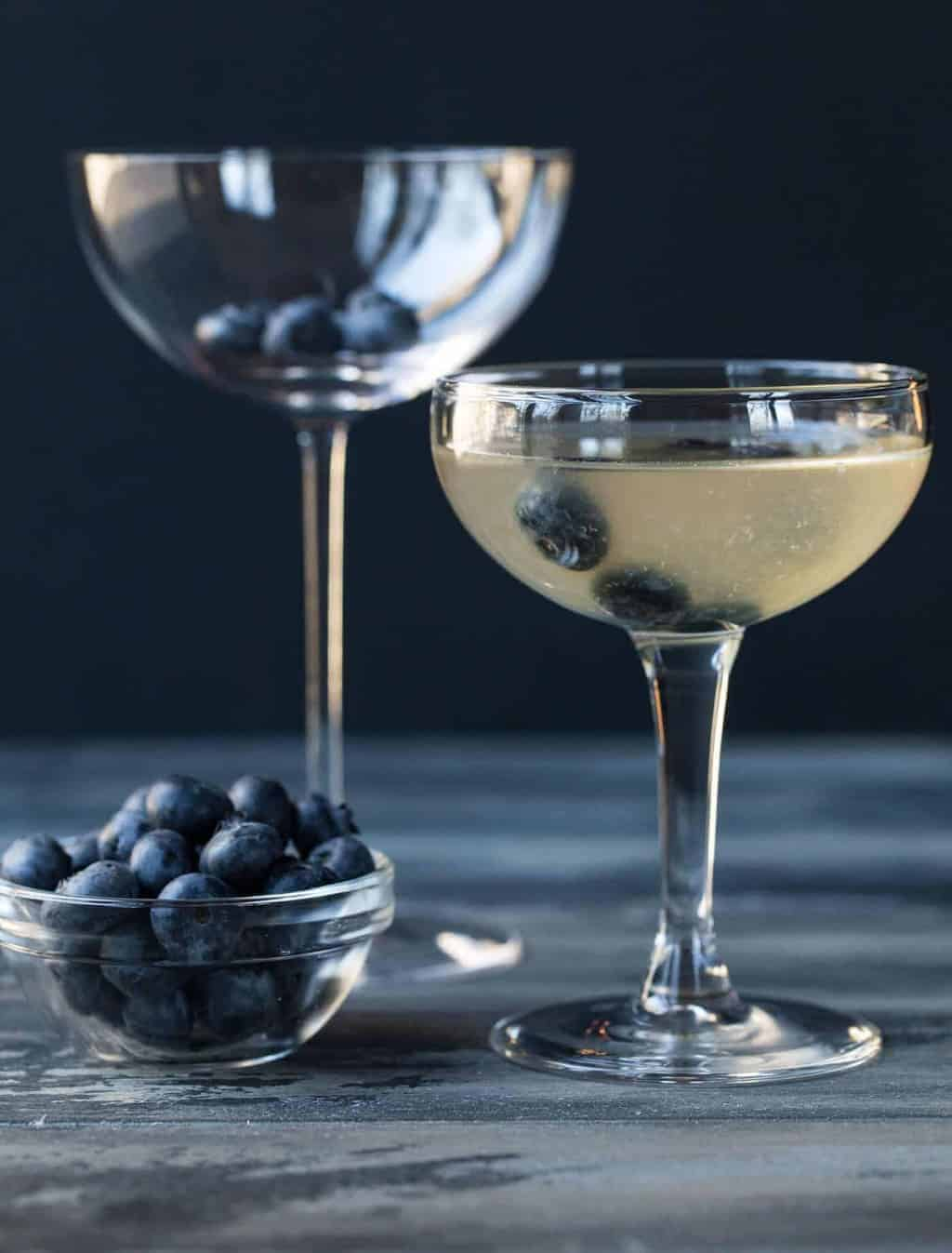 Blueberry Martini in a coupe glass with blueberry floating in it for garnish.