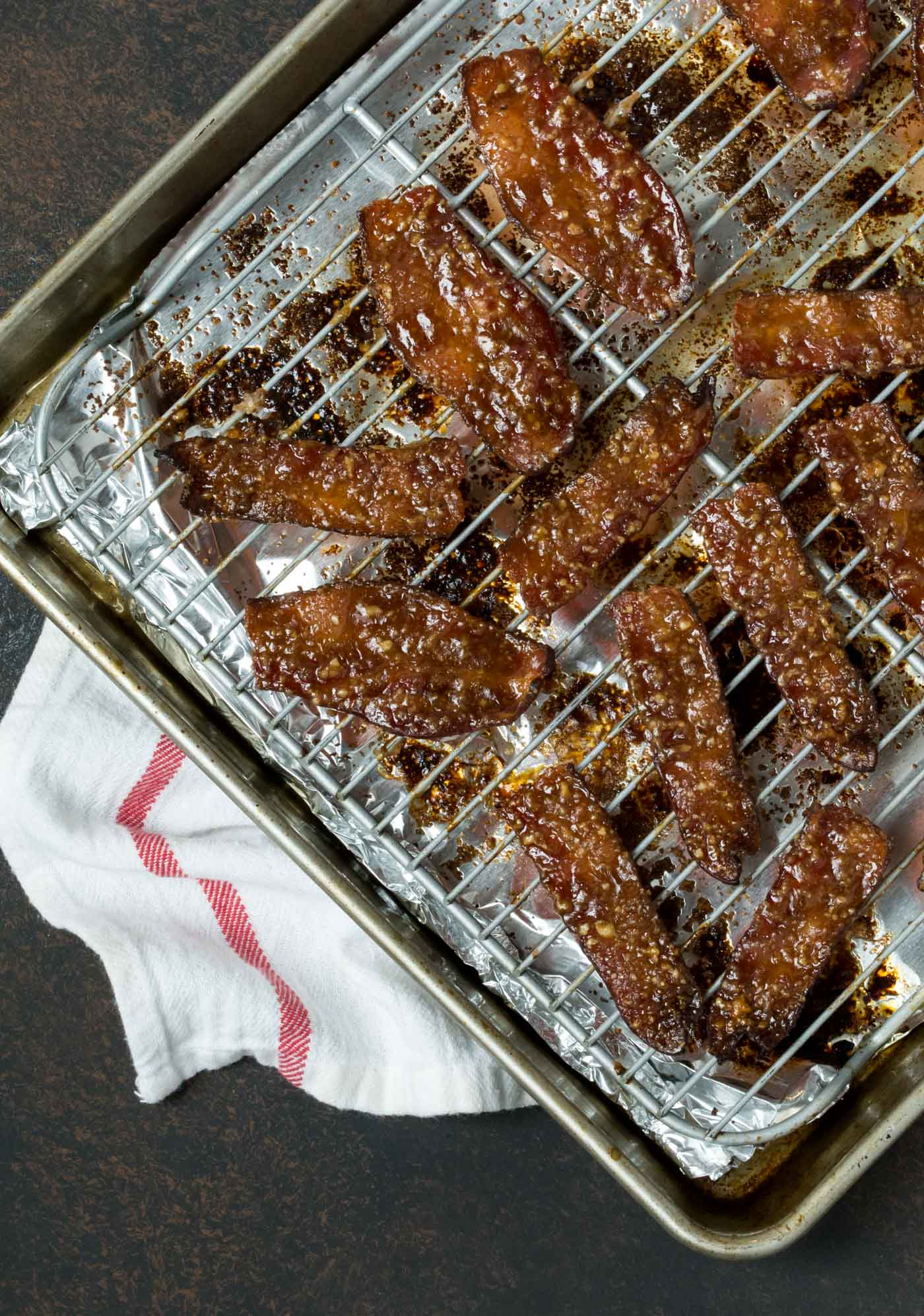 Candied Bacon strips on cooling rack with white linen underneath.