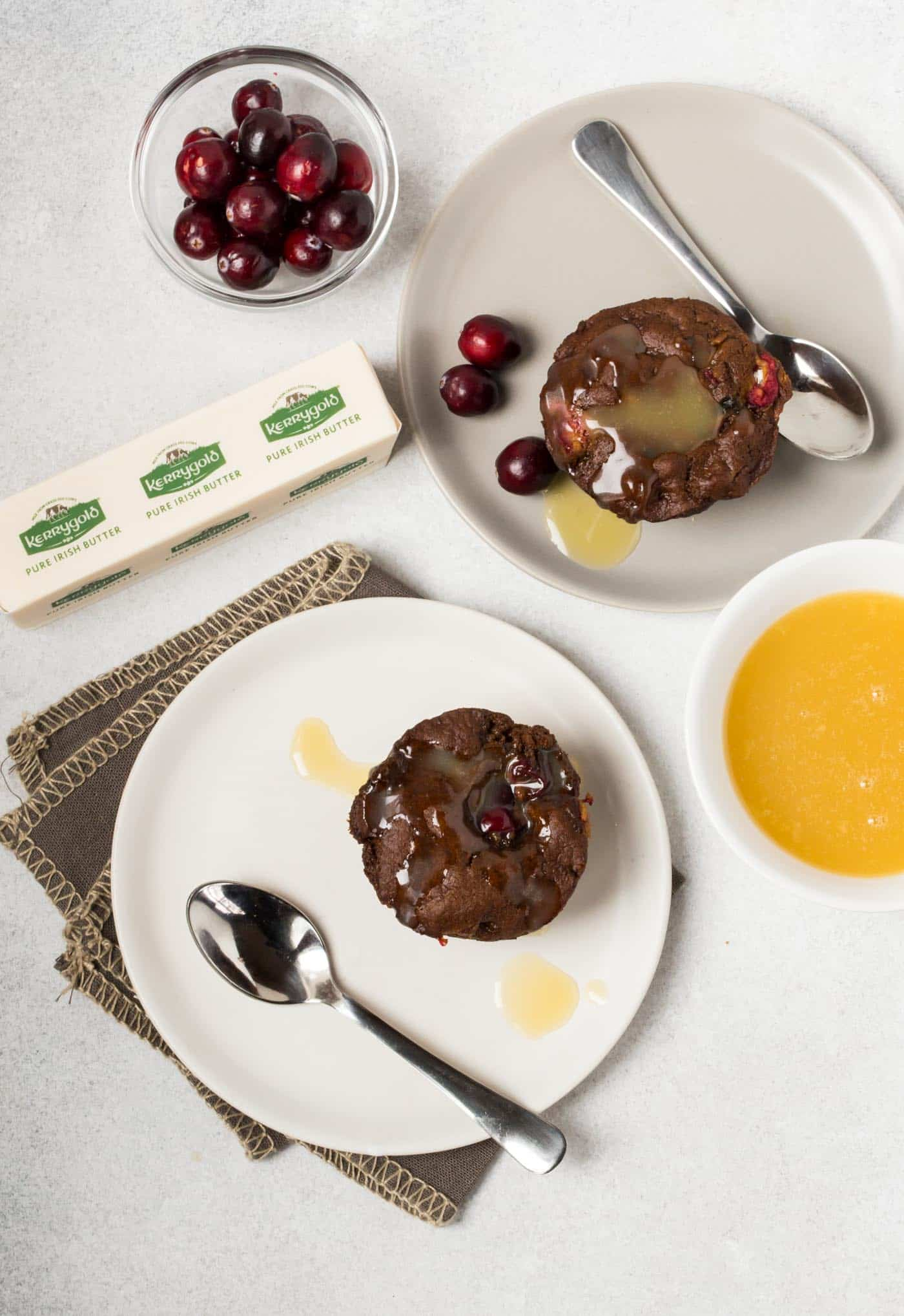 Cranberry Puddings with Warm Vanilla Butter Sauce on white plates with spoons.