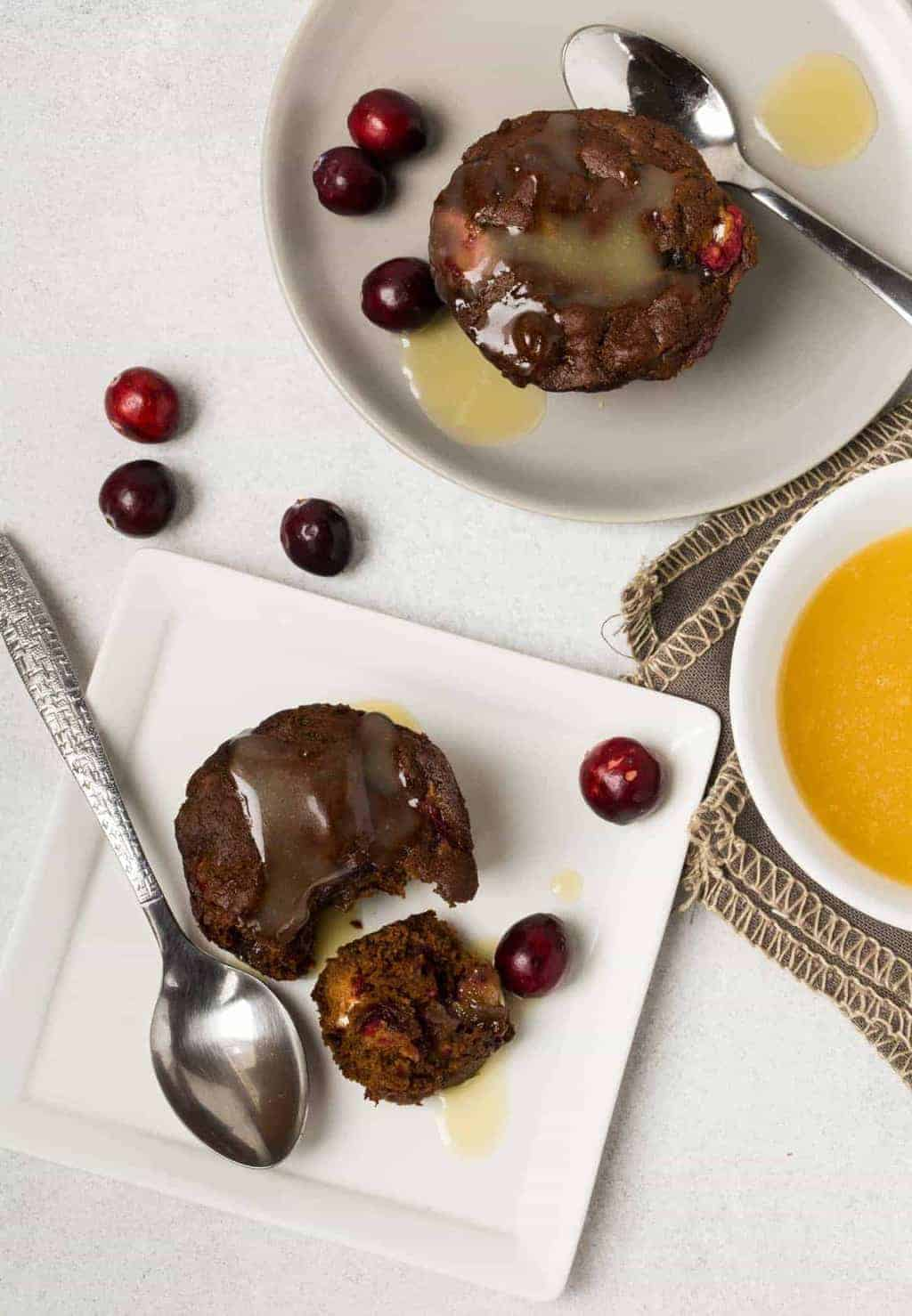 Cranbbery Puddings with Warm Vanilla Butter Sauce with fresh cranberries for garnish.