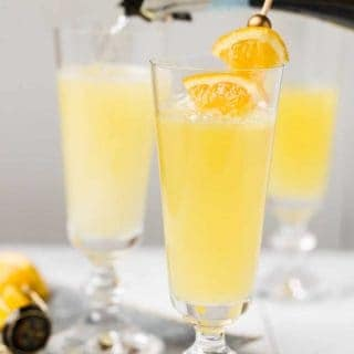 Trio of Grand Orange Mimosas in champagne flutes on white background with a silver tray. Garnished with fresh orange wedges.