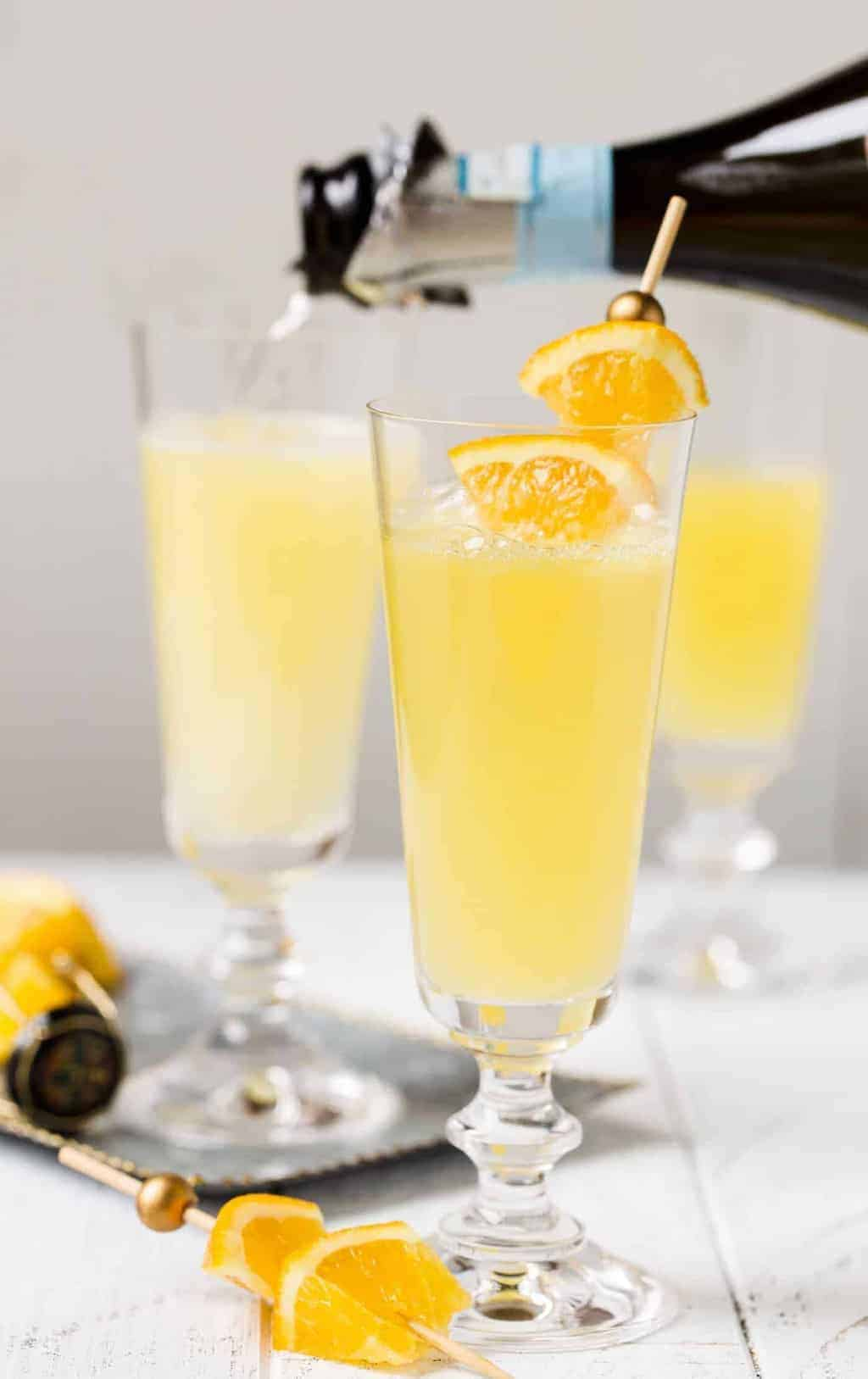 Trio of Mimosas in champagne flutes on white background with a silver tray. Garnished with fresh orange wedges.