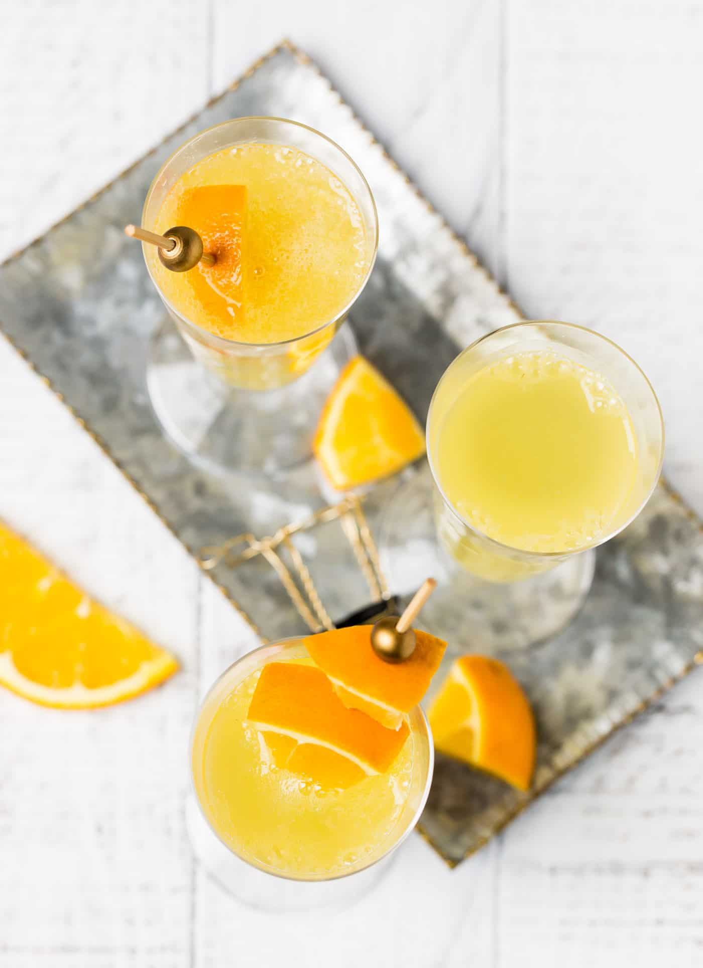 Top down shot of Grand Orange Mimosa recipe on a silver tray with orange slices for garnish.