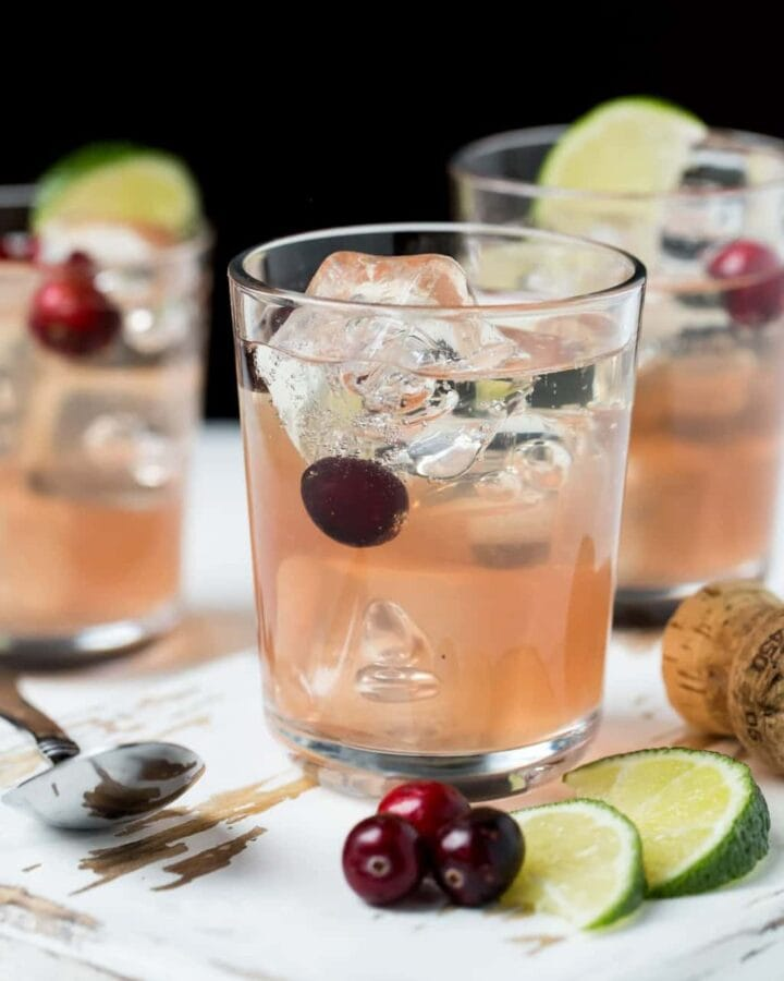 Three glasses of Sparkling Cranberry Gin Cocktails with fresh cranberries and lime wedges as garnishes.