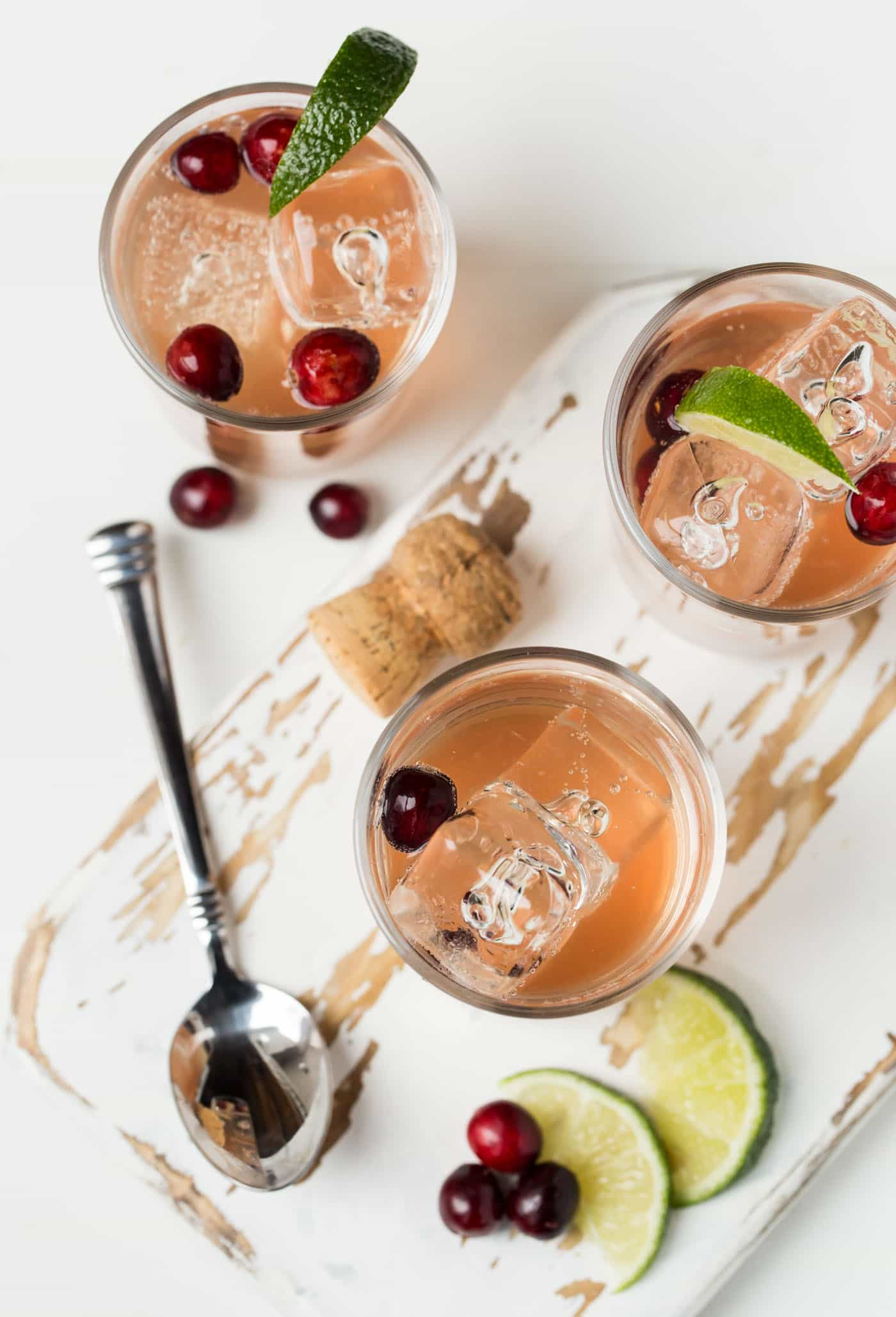 Top down view of three glasses of Sparkling Cranberry Gin Cocktails on a white distressed board. Glasses are garnished with fresh cranberries and lime wedges.