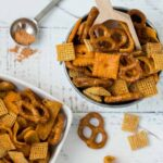Two bowls of Homemade Taco Snack Mix with small wooden scoop of snack mix in one of the bowls.
