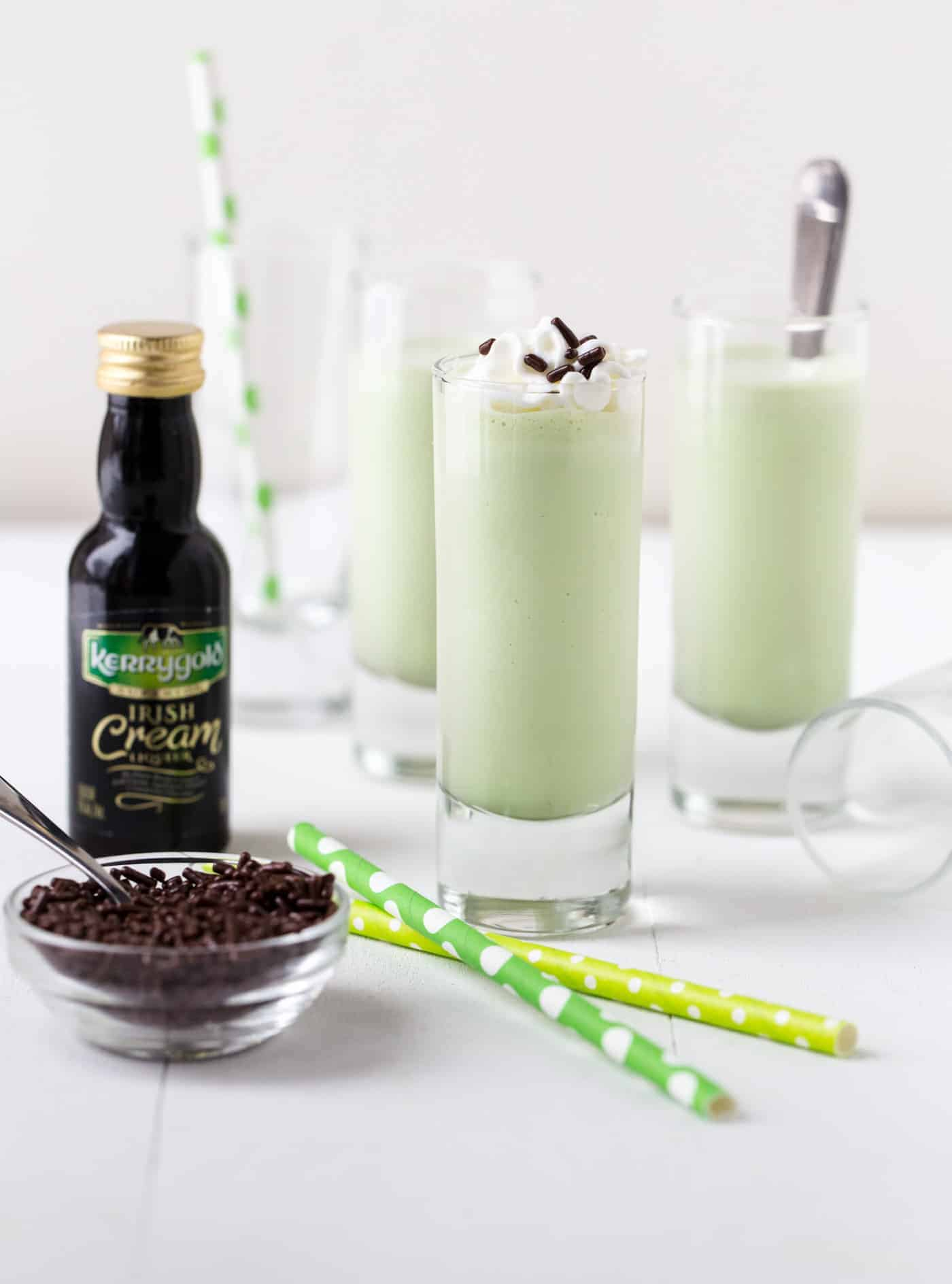 Shot glasses filled with Mini Irish Cream Shakes. Shot glasses are garnished with straws, small spoons, whipped cream and chocolate sprinkles.