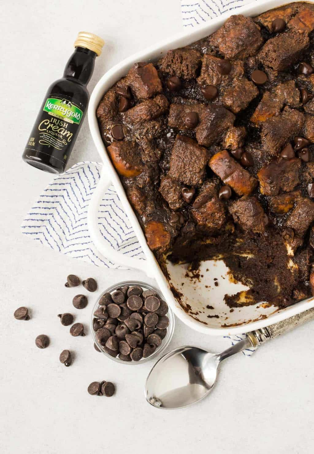 White casserole dish filled with Chocolate Irish Cream Bread Pudding. Small bowl of dark chocolate chips and a bottle of Kerrygold Irish Cream Liqueur are nearby.
