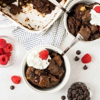 Small white bowls of Chocolate Irish Cream Bread pudding with fresh raspberries and whipped cream topping.
