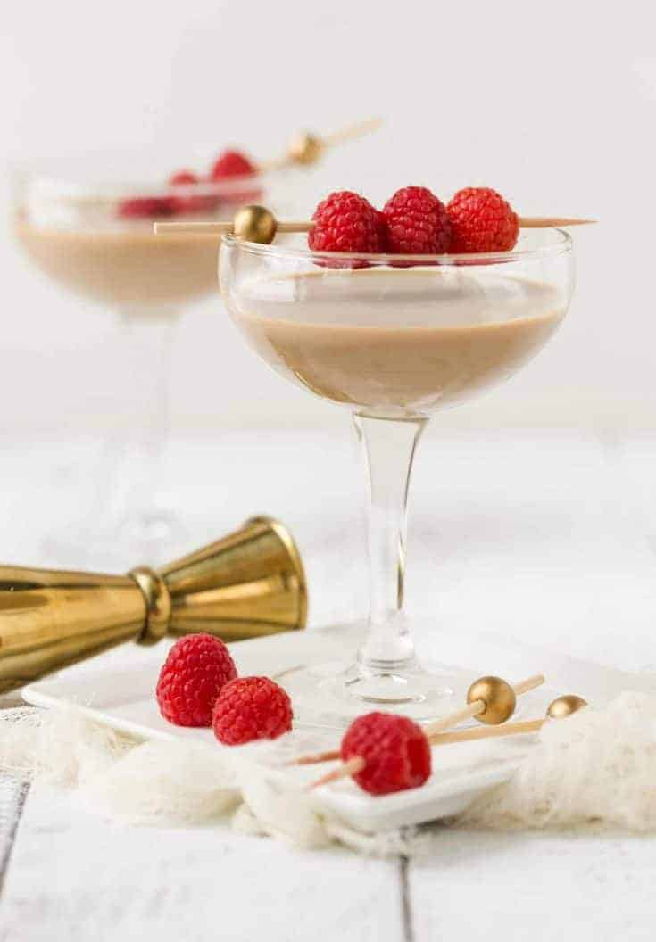 Chocolate Raspberry Martinis in coupe glasses with fresh raspberries threaded on skewer for garnish.