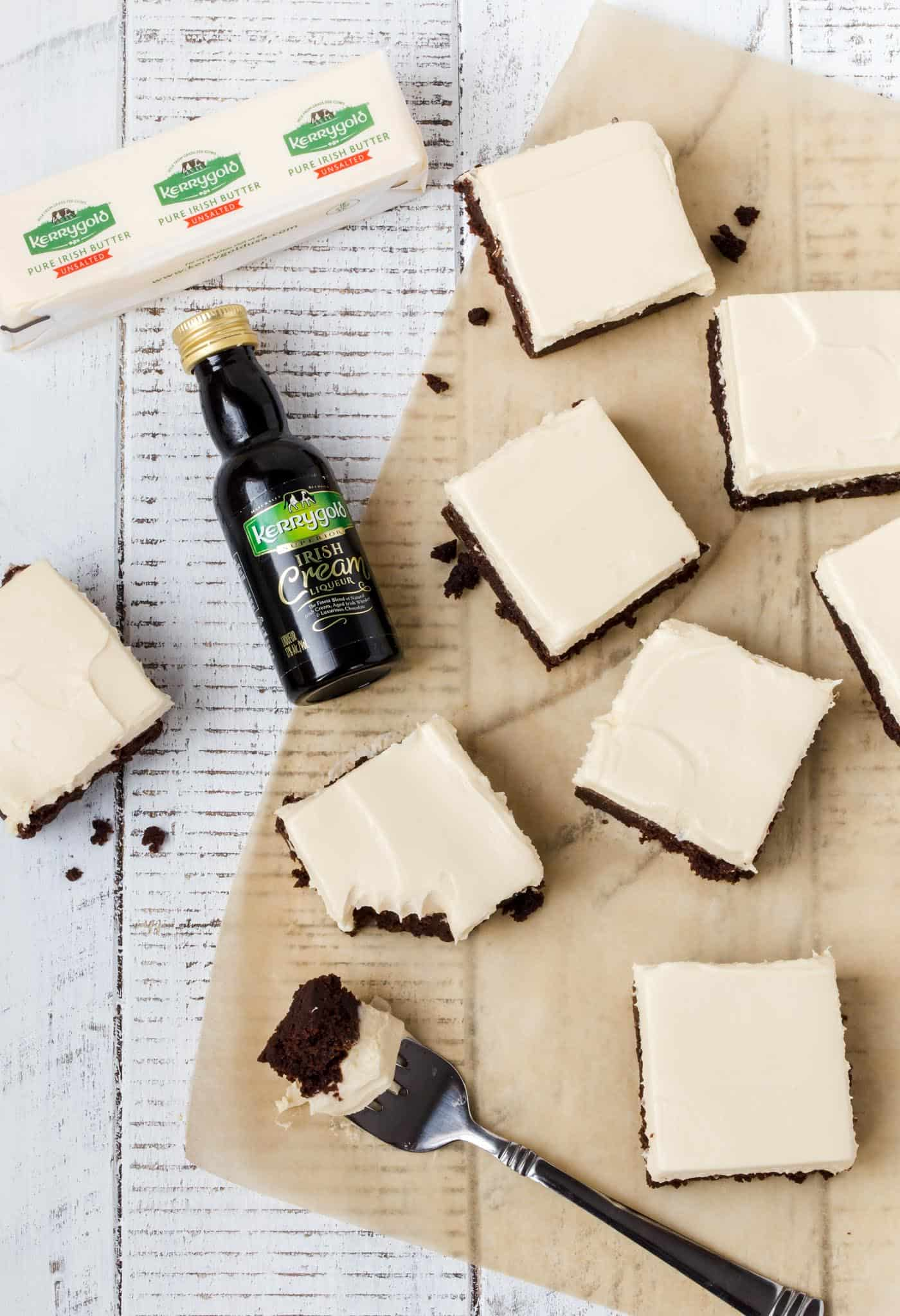 Top down shot of cut Irish Cream Brownies on parchment paper on a white background with small bottle of irish cream liqueur.