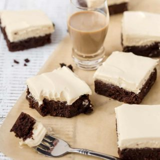 Irish Cream Brownies cut into squares on parchment paper with a brownie filled fork in front.