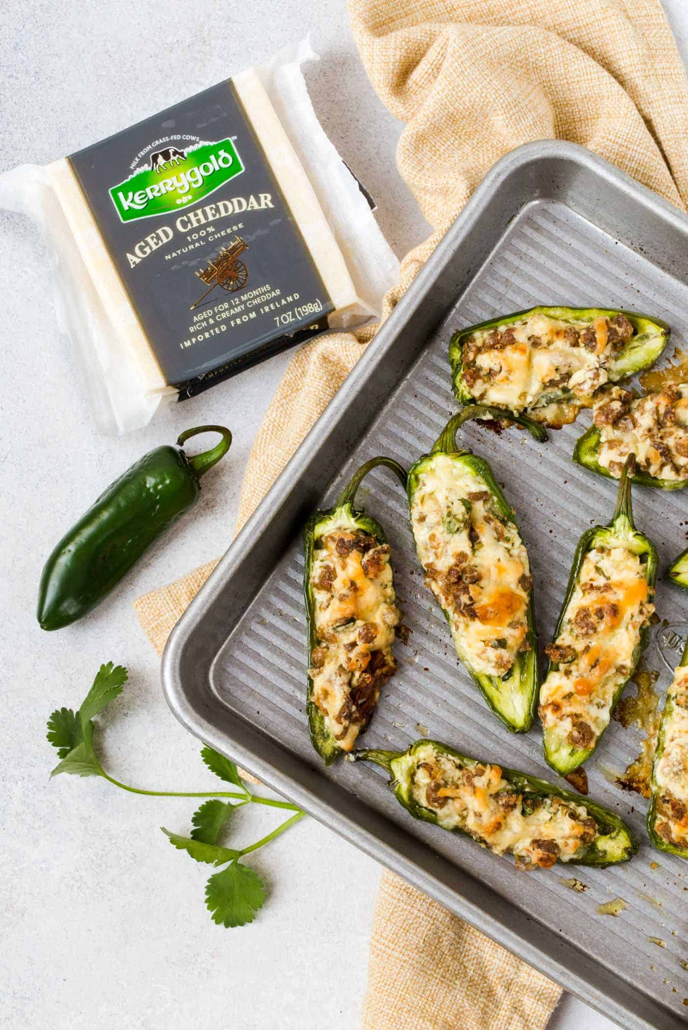 Top down shot of Cheddar Jalapeño Poppers with Sausage on baking sheet with cheese block and small jalapeño for garnish.