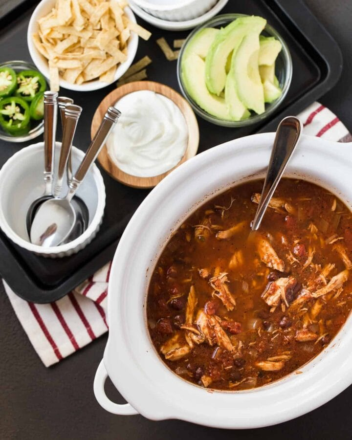 Slow Cooker full of Chicken Tortilla Soup. Bowls of sour cream, avocado, jalapeno slices and tortilla strips for toppings.