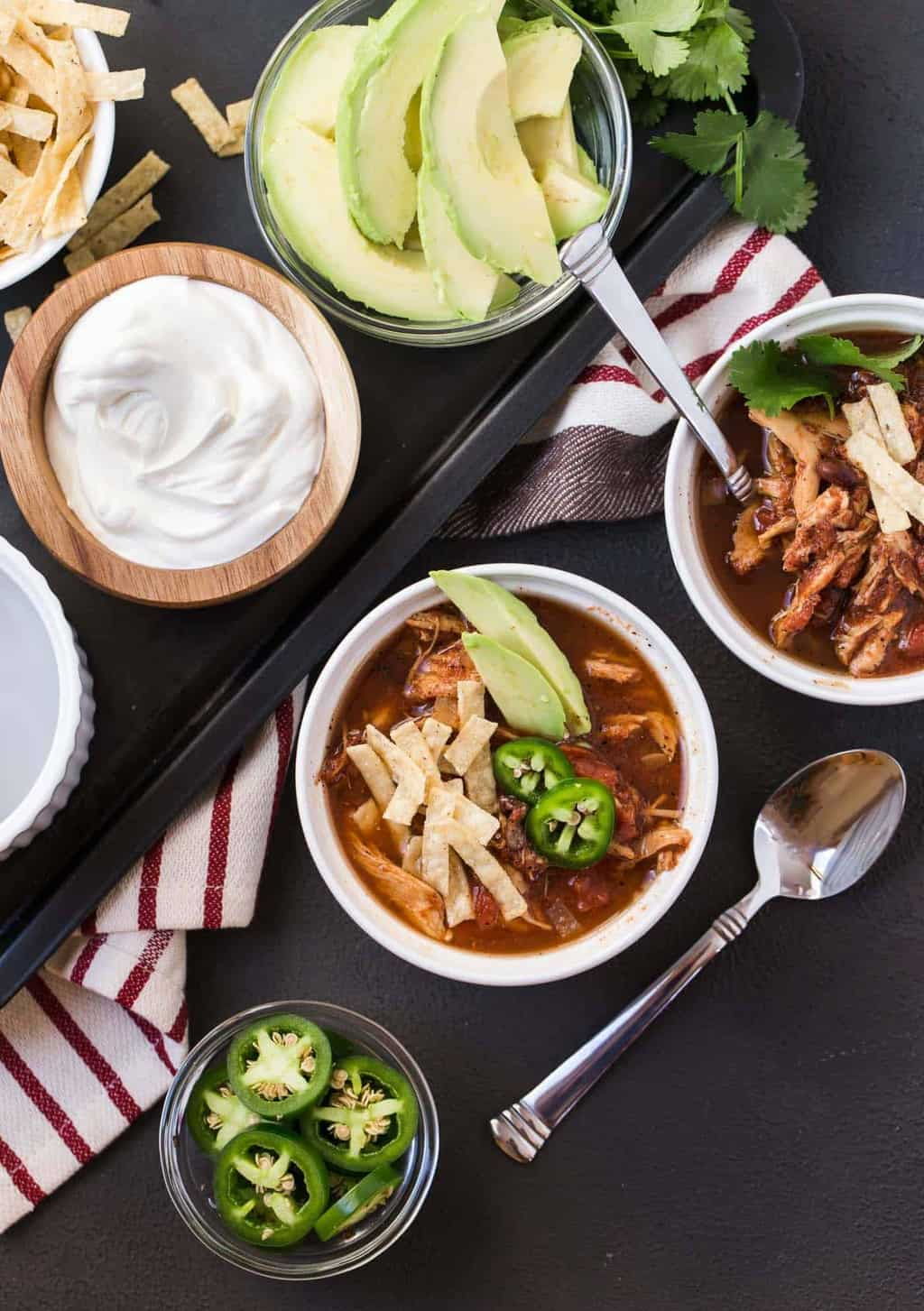 Two bowls of Slow Cooker Chicken Tortilla Soup topped with fresh cilantro, jalapeno slices, sour cream, avocado and tortilla strips.