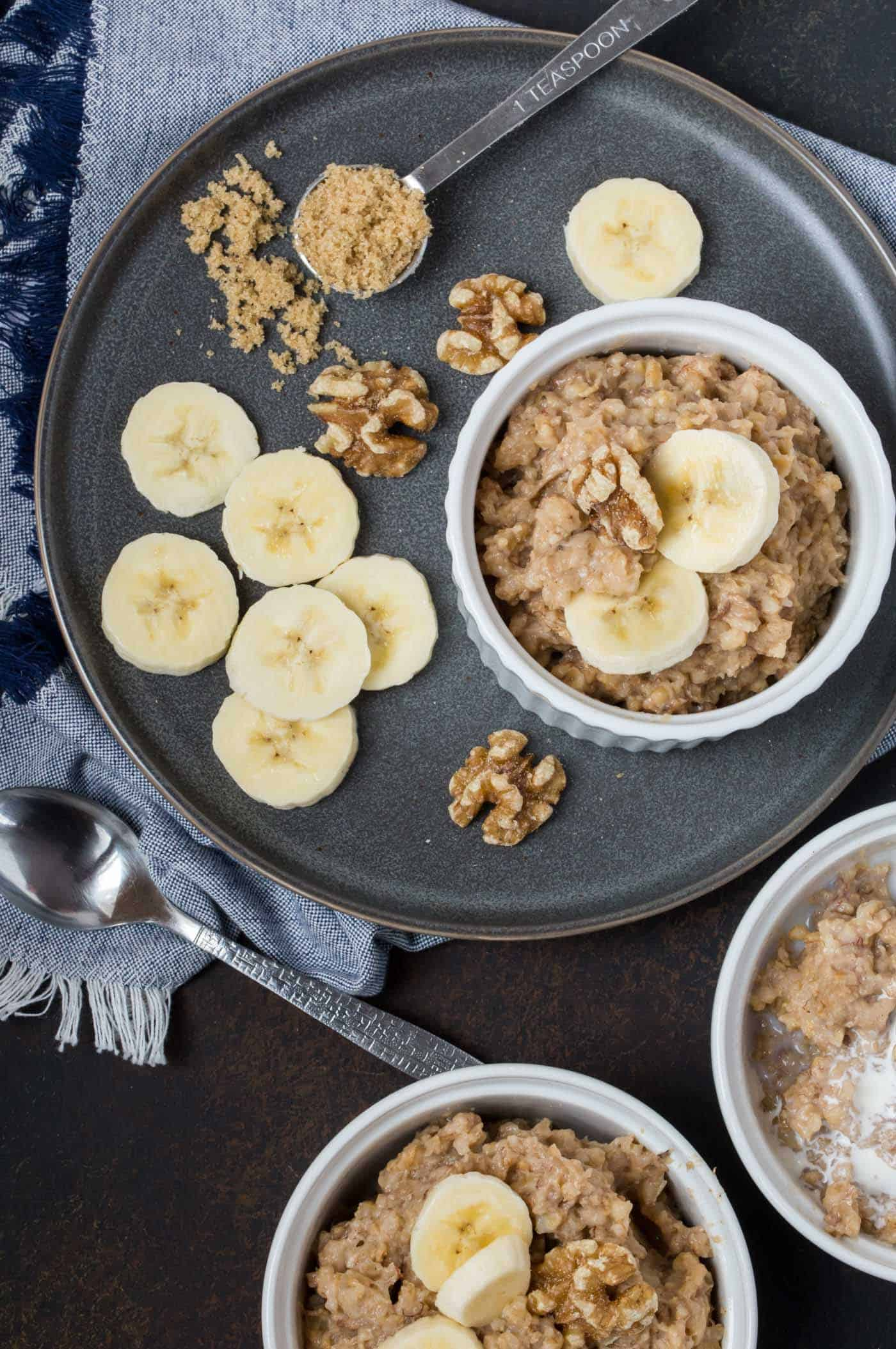 Three white ramekins filled with Slow Cooker Steel Cut Oatmeal with Bananas. Garnished with brown sugar, fresh banana slices and walnuts.