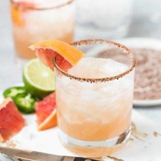 Glasses of Spicy Grapefruit Margaritas with a salty and sweet chili powder rim. Garnished with fresh lime and grapefruit wedges and jalapeno slices.