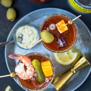 Top down shot of Bloody Mary in a tall glass filled with ice and garnished with fresh lemon slices, cheese and pickles.