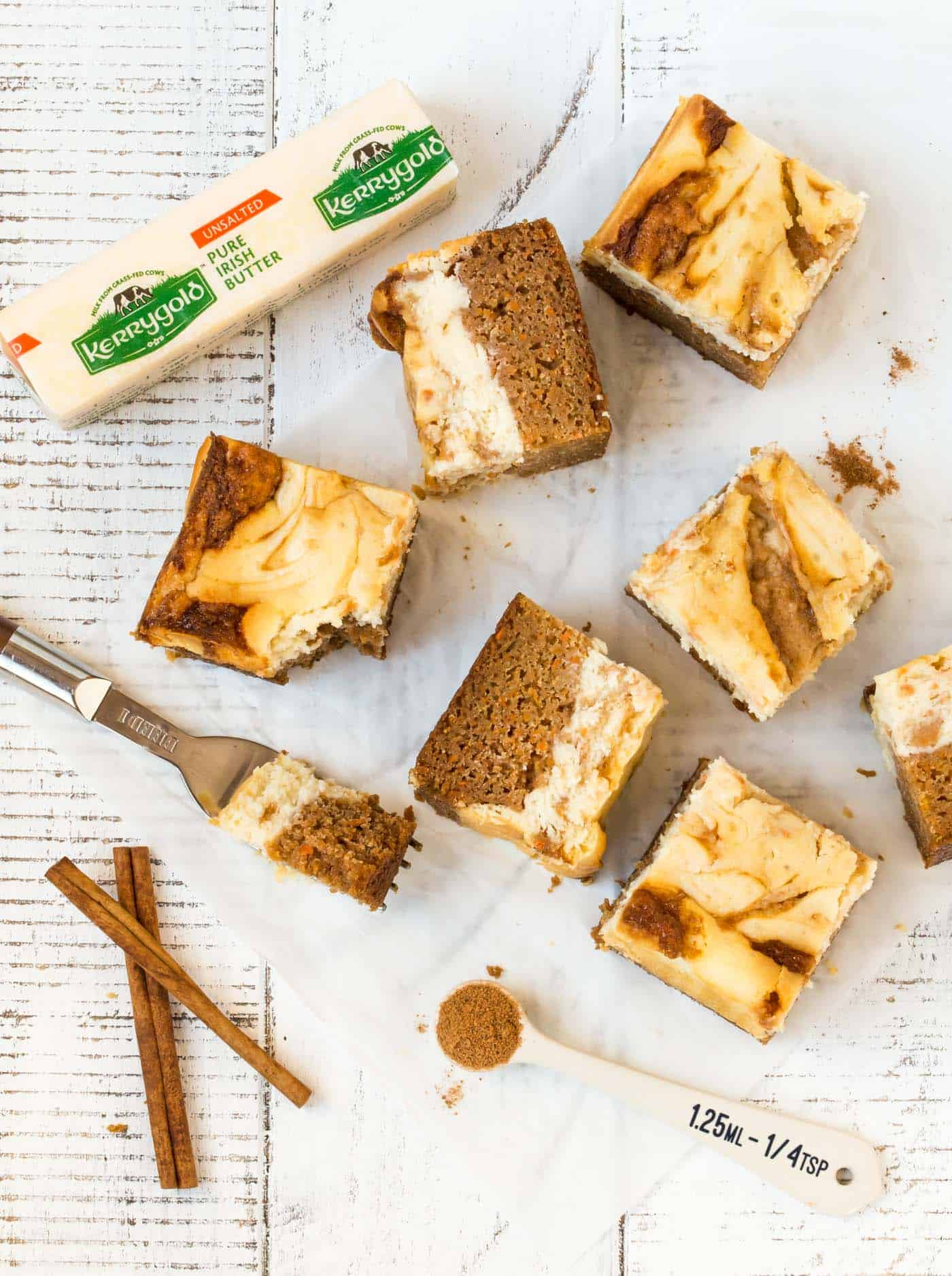 Top down shot of cut carrot cake cheesecake bars on white background with fresh cinnamon sticks for garnish.