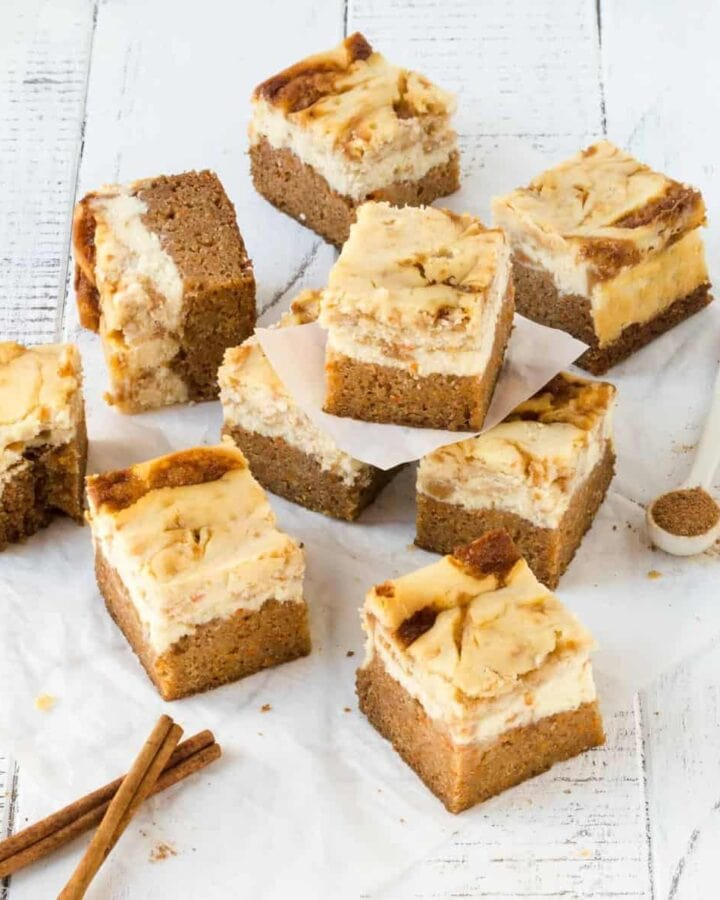 Carrot Cake Cheesecake Bars cut into squares on white surface with ground cinnamon for garnish.
