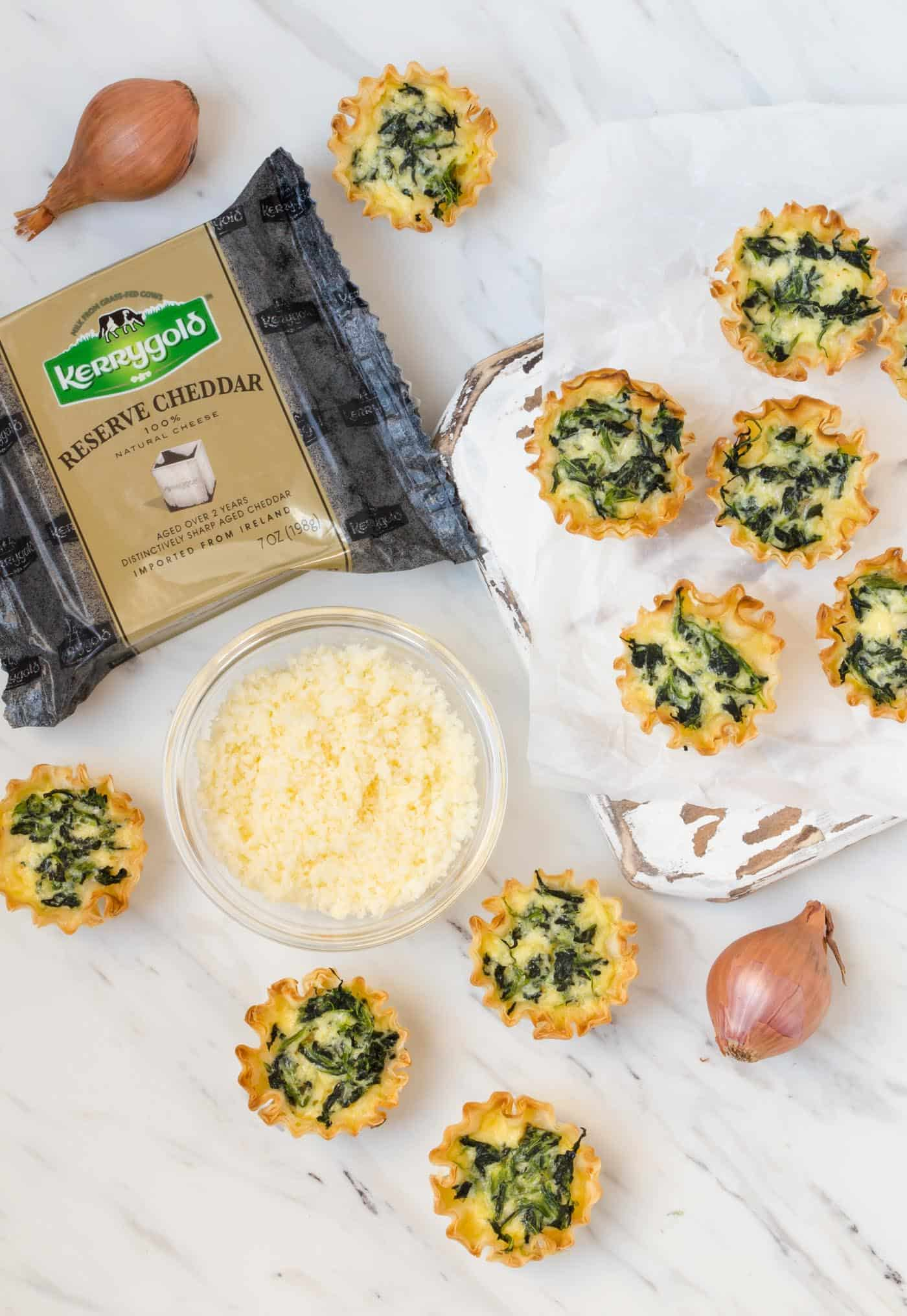 Mini Spinach Quiche on a white background surrounded by shallots and grated Kerrygold Reserve Cheddar Cheese
