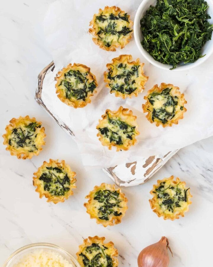 Mini Spinach Quiche on a white background surrounded by grated cheddar cheese, shallots and chopped spinach.