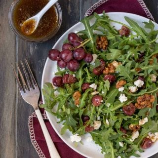 Top down shot of Arugula Salad with Roasted Grapes and Feta Cheese drizzled with dressing and garnished with roasted walnuts.