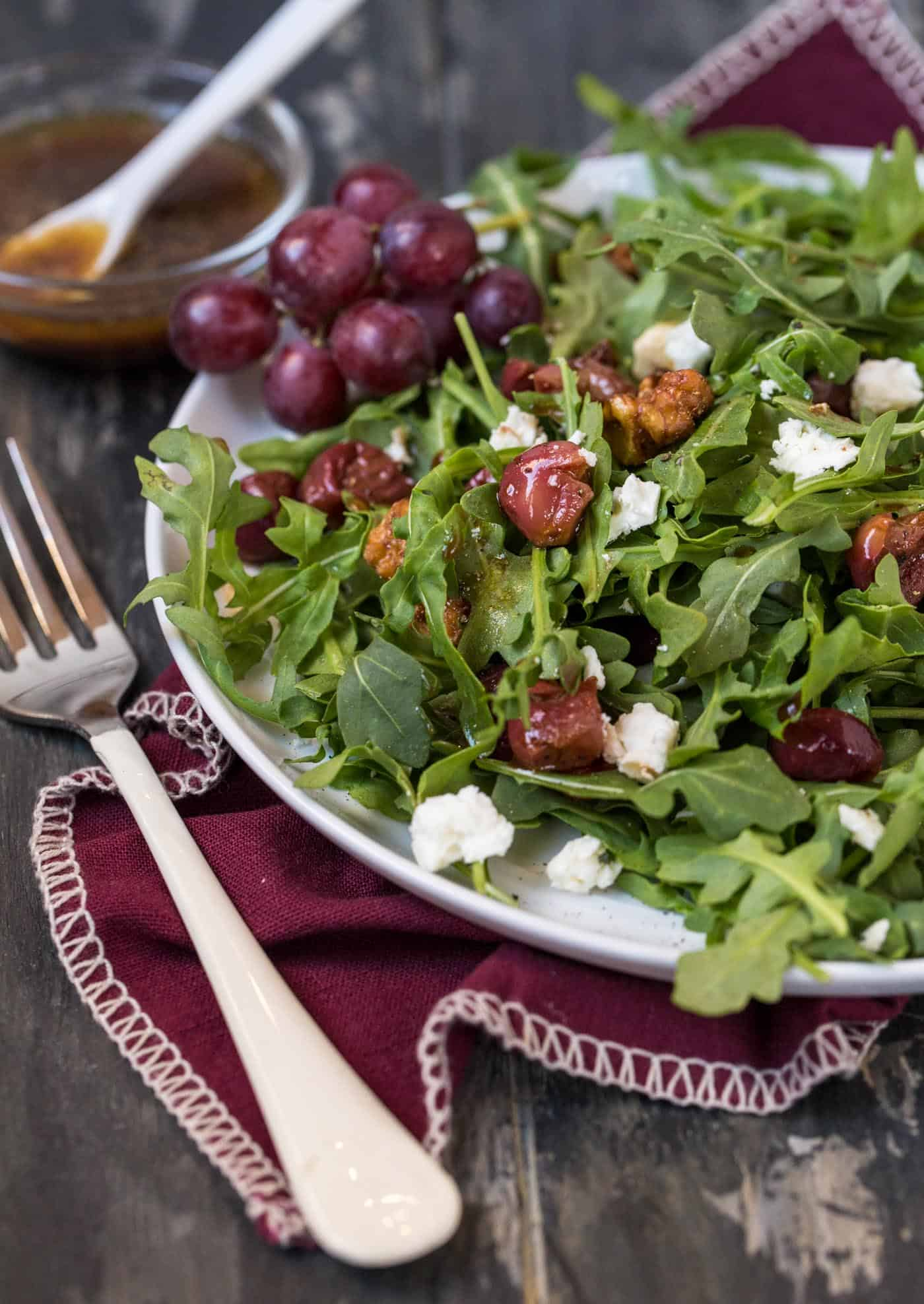 Side shot of Arugula Salad with Roasted Grapes and Feta Cheese on purple napkin with a white fork. Garnished with bunch a small bunch of fresh grapes.