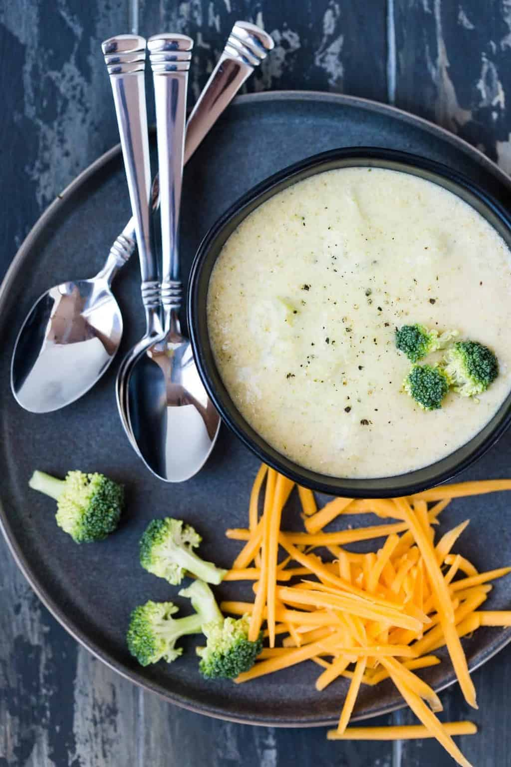 Broccoli Cheese Soup in small black bowl with shredded cheddar cheese and fresh broccoli for garnish.