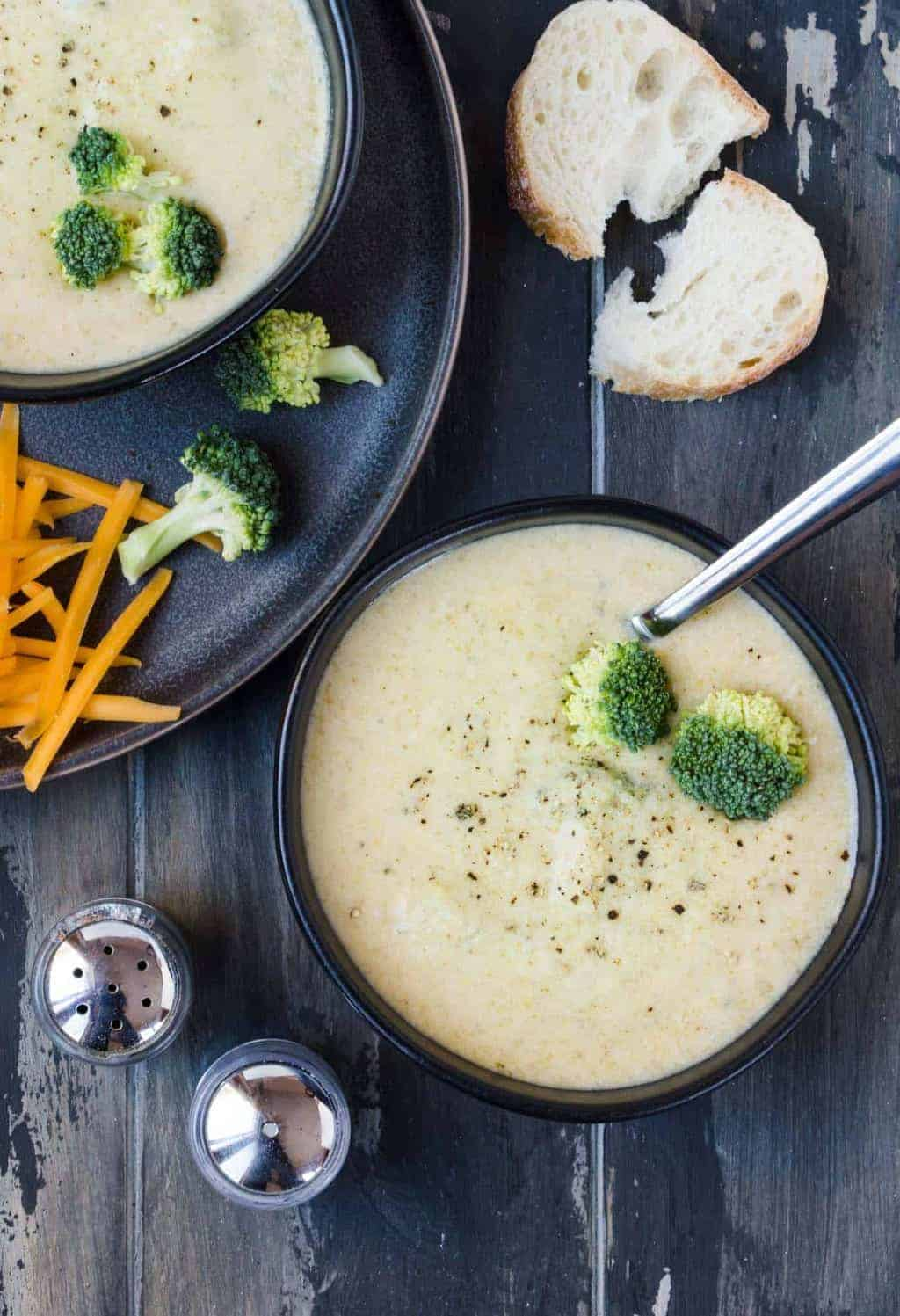 Top down shot of broccoli cheese soup in black bowls on a dark background with freshly grated pepper on top.