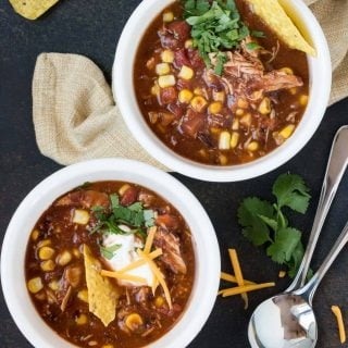 two bowls of slow cooker chicken taco soup garnished with fresh cilantro, sour cream and chips.