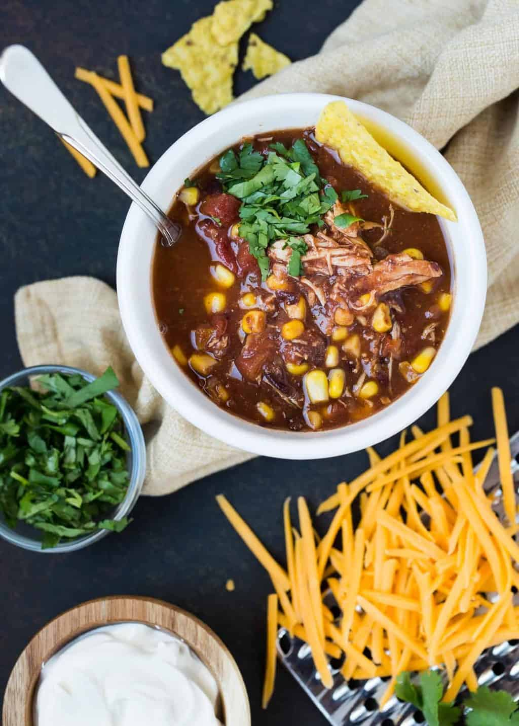 SLow Cooker Chicken Taco Soup in white crock pot with fresh cilantro and shredded cheese for garnish.