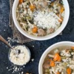 Two bowls of Slow Cooker Italian Wedding Soup recipe garnished with baguette sliced and grated Parmesan cheese.