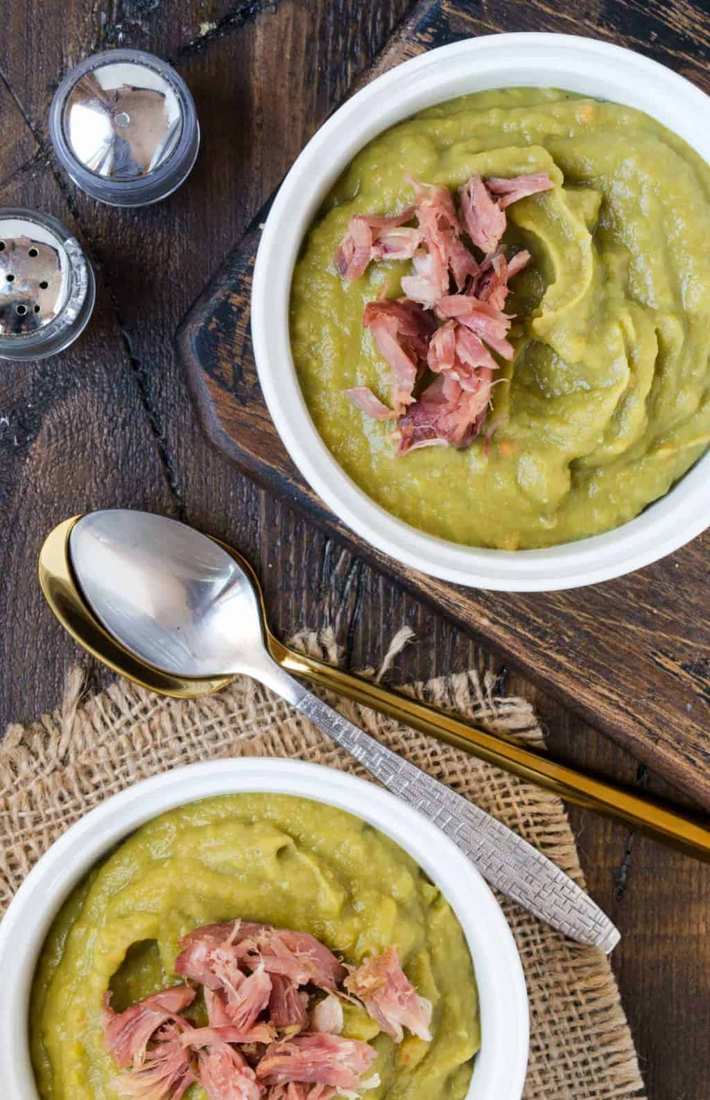 Two bowls of Slow Cooker Split Pea Soup with Ham and two spoons. Soup is topped with shredded ham.