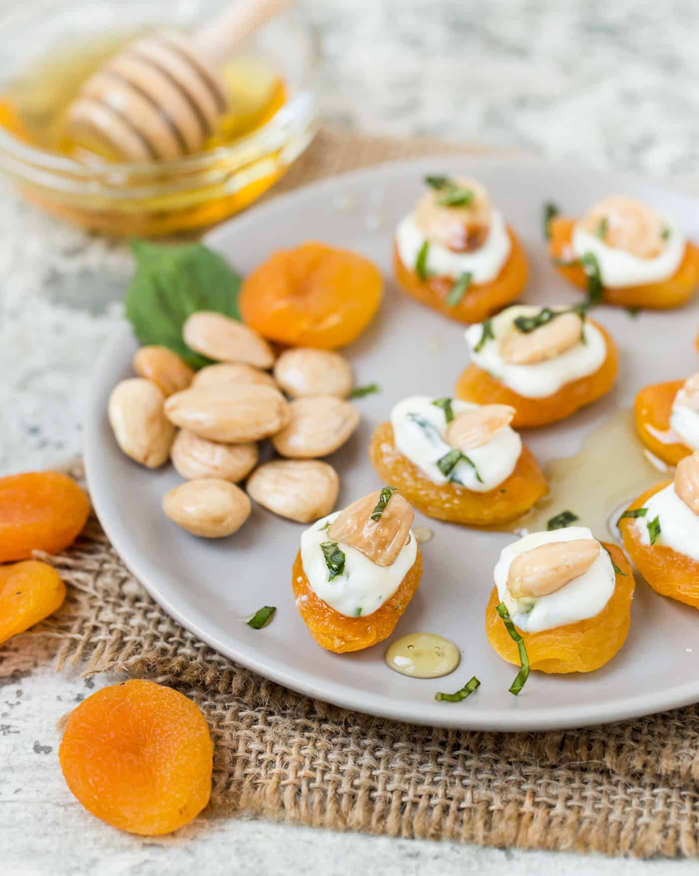 Gray plate filled with indivdual stuffed apricots with goat cheese, basil and marcona almonds.