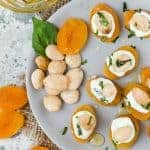 Stuffed Apricots with Goat Cheese, Basil and Marcona Almonds on a gray plate with fresh basil leaves and almonds for garnish.