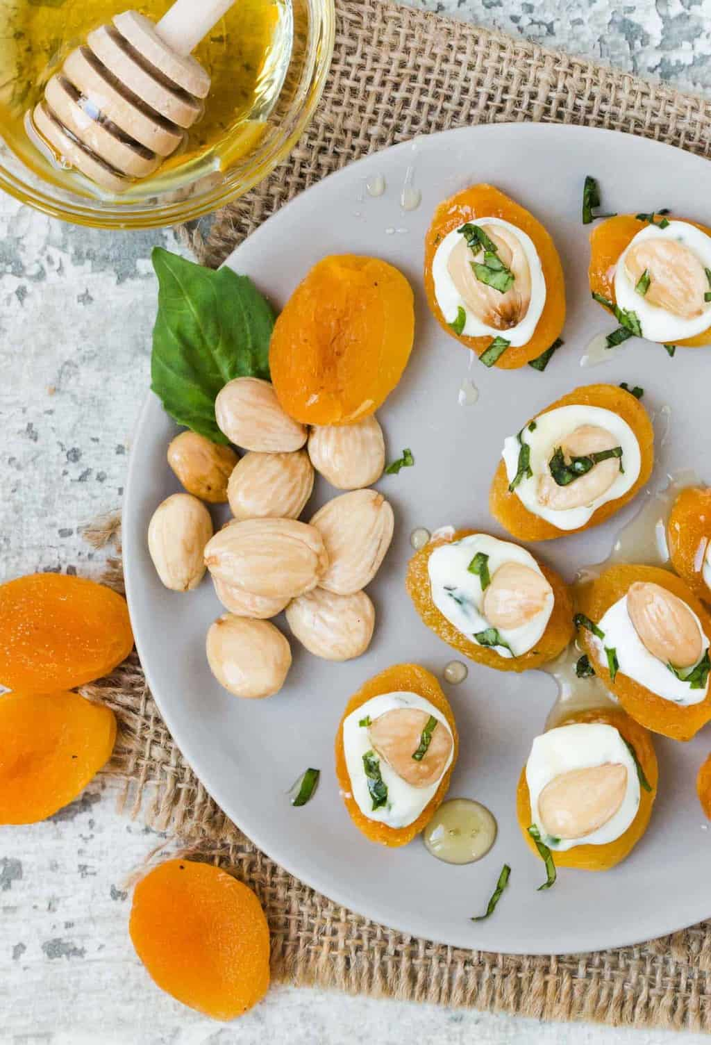 Top down shot of Stuffed Apricots with Goat Cheese, Basil and Marcona Almonds on a gray plate with fresh basil leaves and almonds for garnish.
