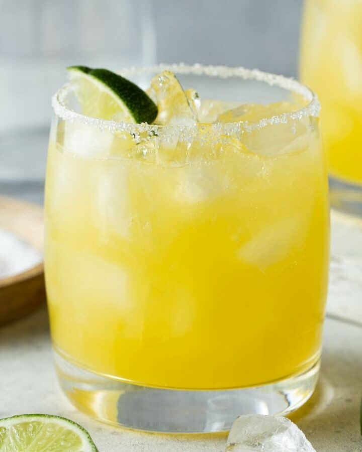 Mango margarita in an ice filled glass rimmed with salt and garnished with lime wedges.