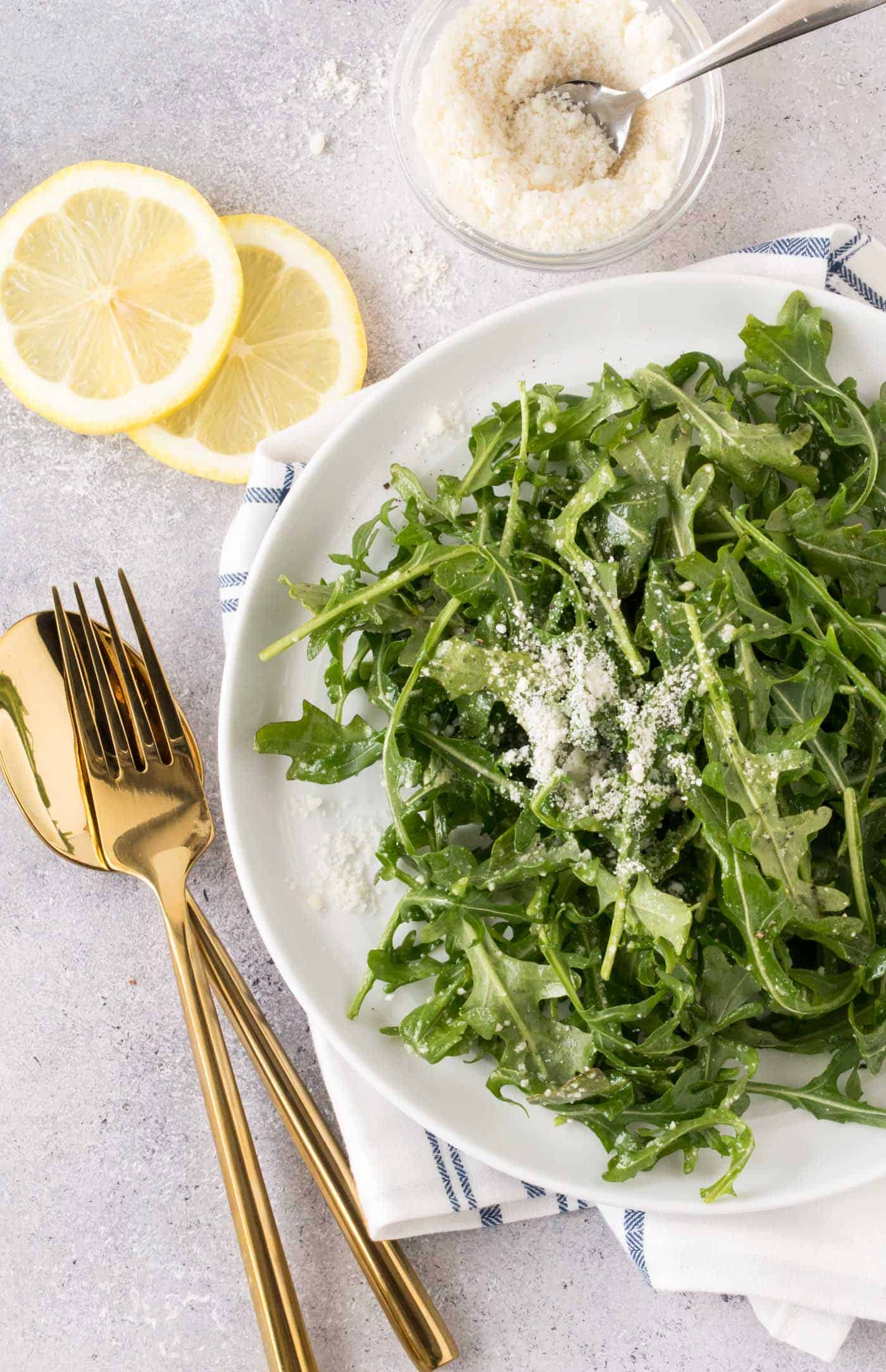 Large white bowl filled with Arugula Salad with Lemon Vinaigrette. Garnished with freshly shaved parmesan cheese and lemon wedges