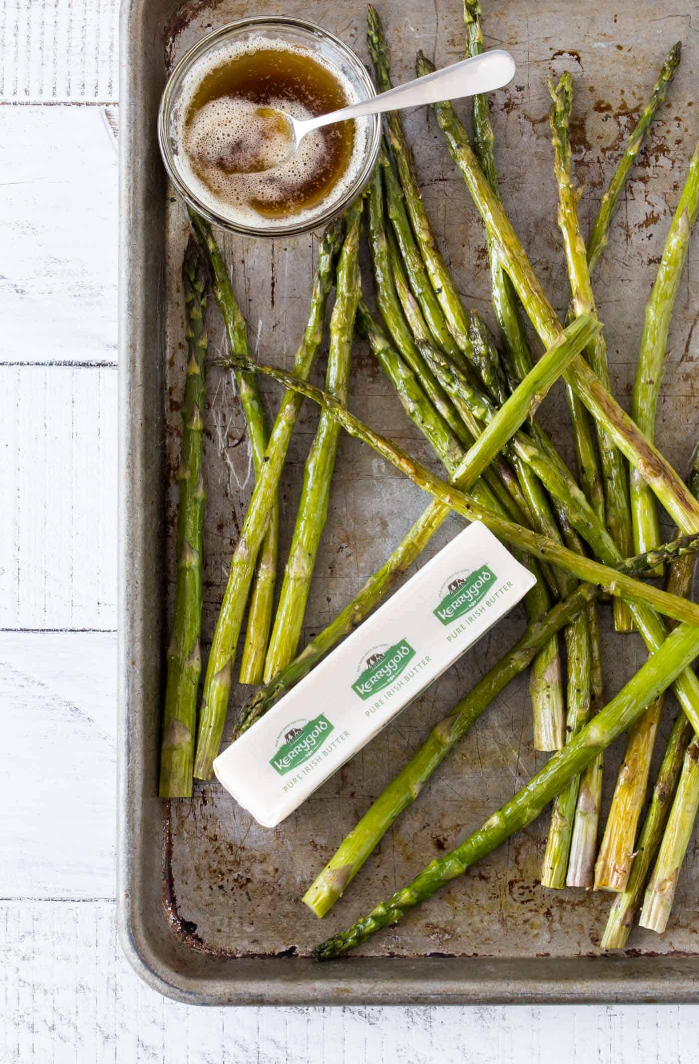 Oven Roasted Asparagus on a sheet pan with a small white bowl of brown butter sauce and a stick of Kerrygold salted butter.