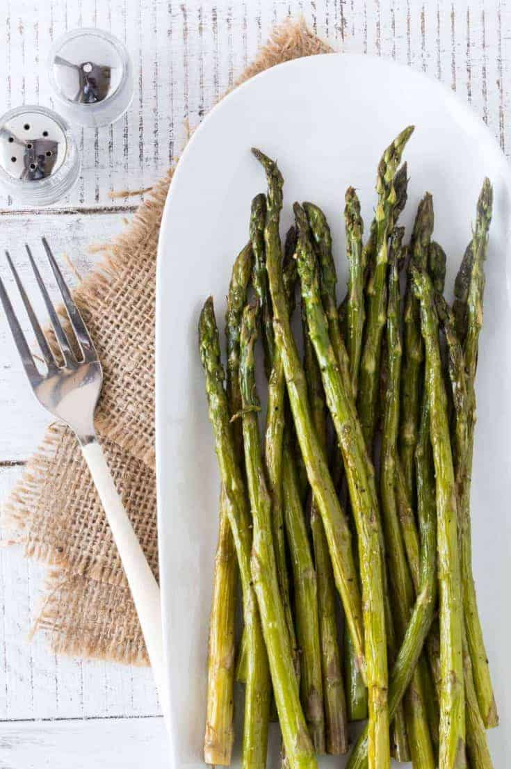 Oven Roasted Asparagus on a white platter drizzled with brown butter sauce.
