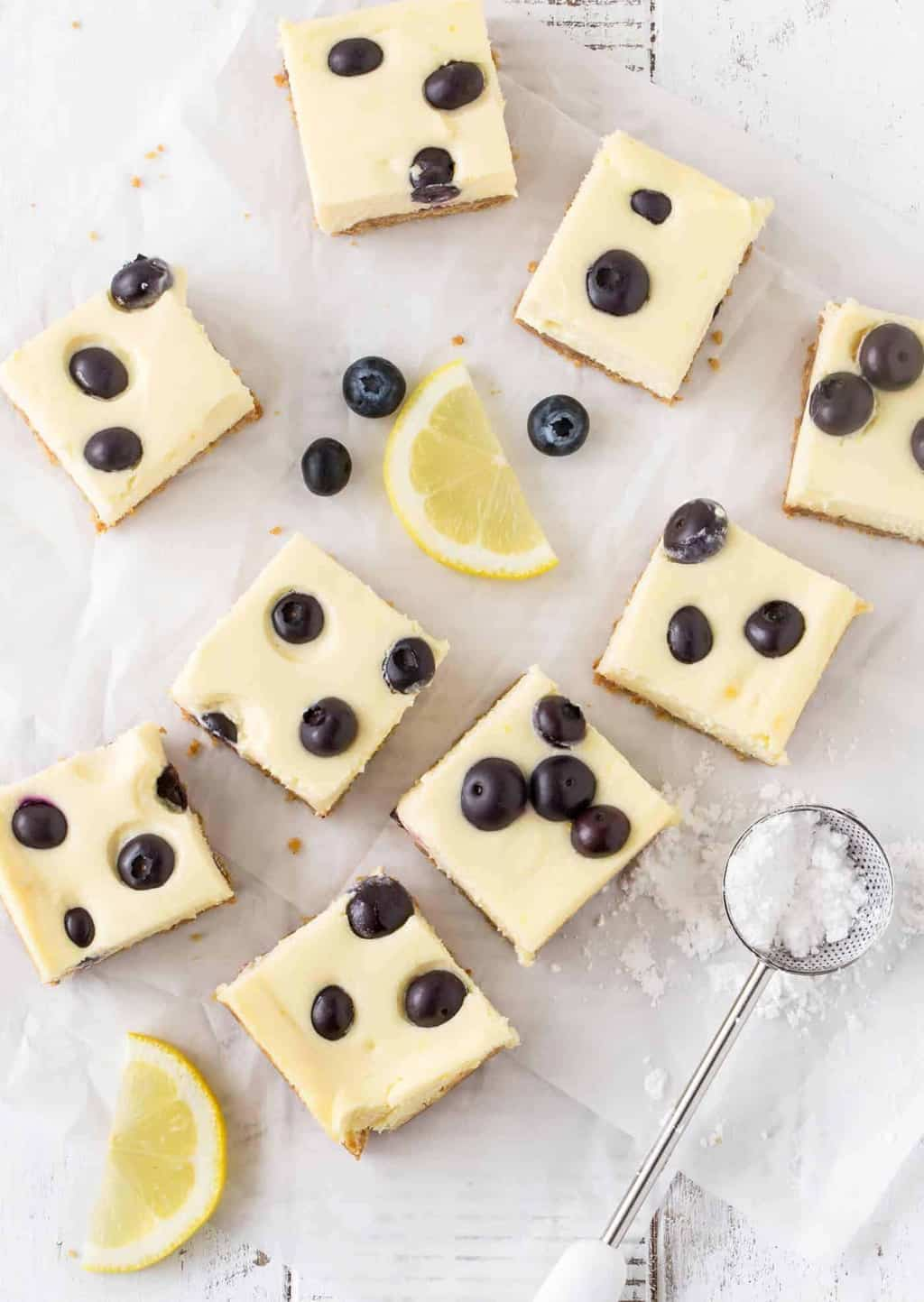 top down shot of Lemon Blueberry Cheesecake Bars recipe on white background with powdered sugar and lemon slices for garnish.