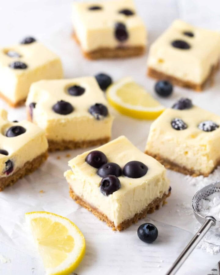 Side shot of lemon blueberry cheesecake bars with fresh blueberries and lemon slices for garnish.