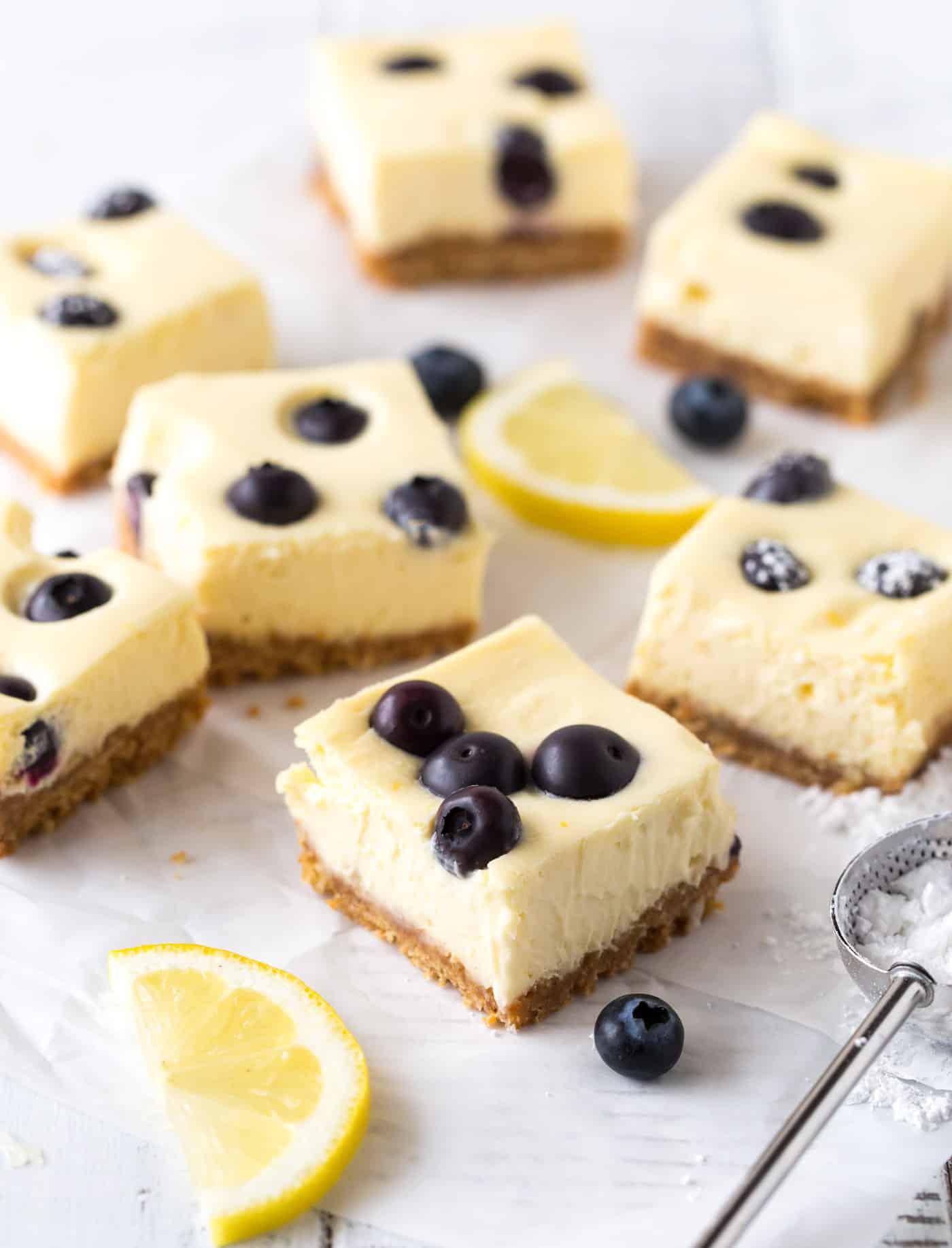 Side shot of lemon blueberry cheesecake bars with fresh blueberries and lemon slices for garnish.