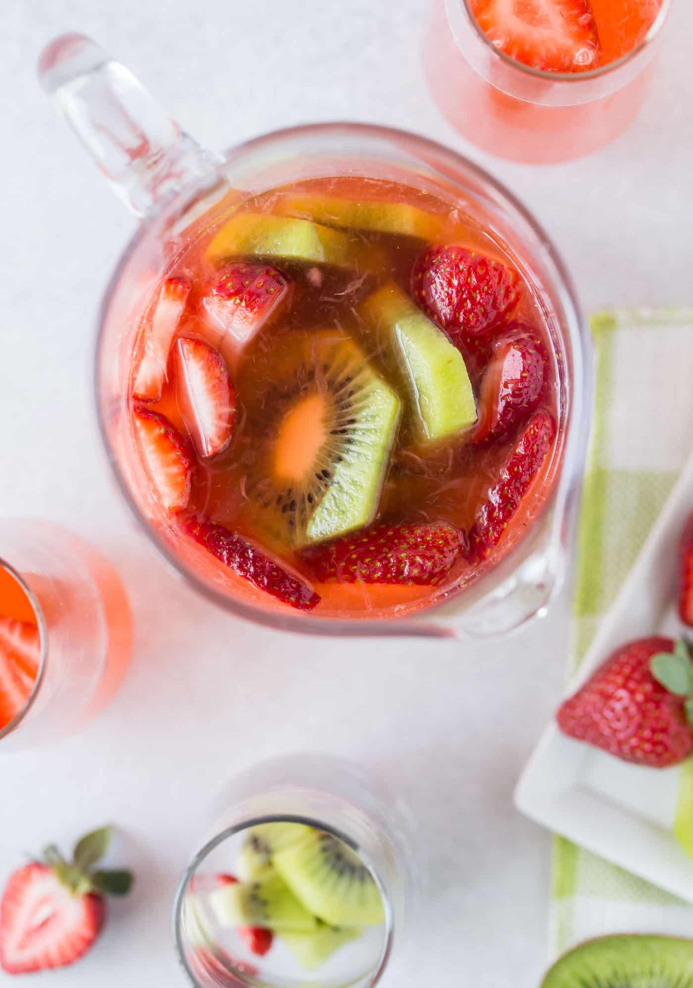 pitcher full of strawberries, kiwi and rym with extra sliced kiwi and strawberries on side for garnish.