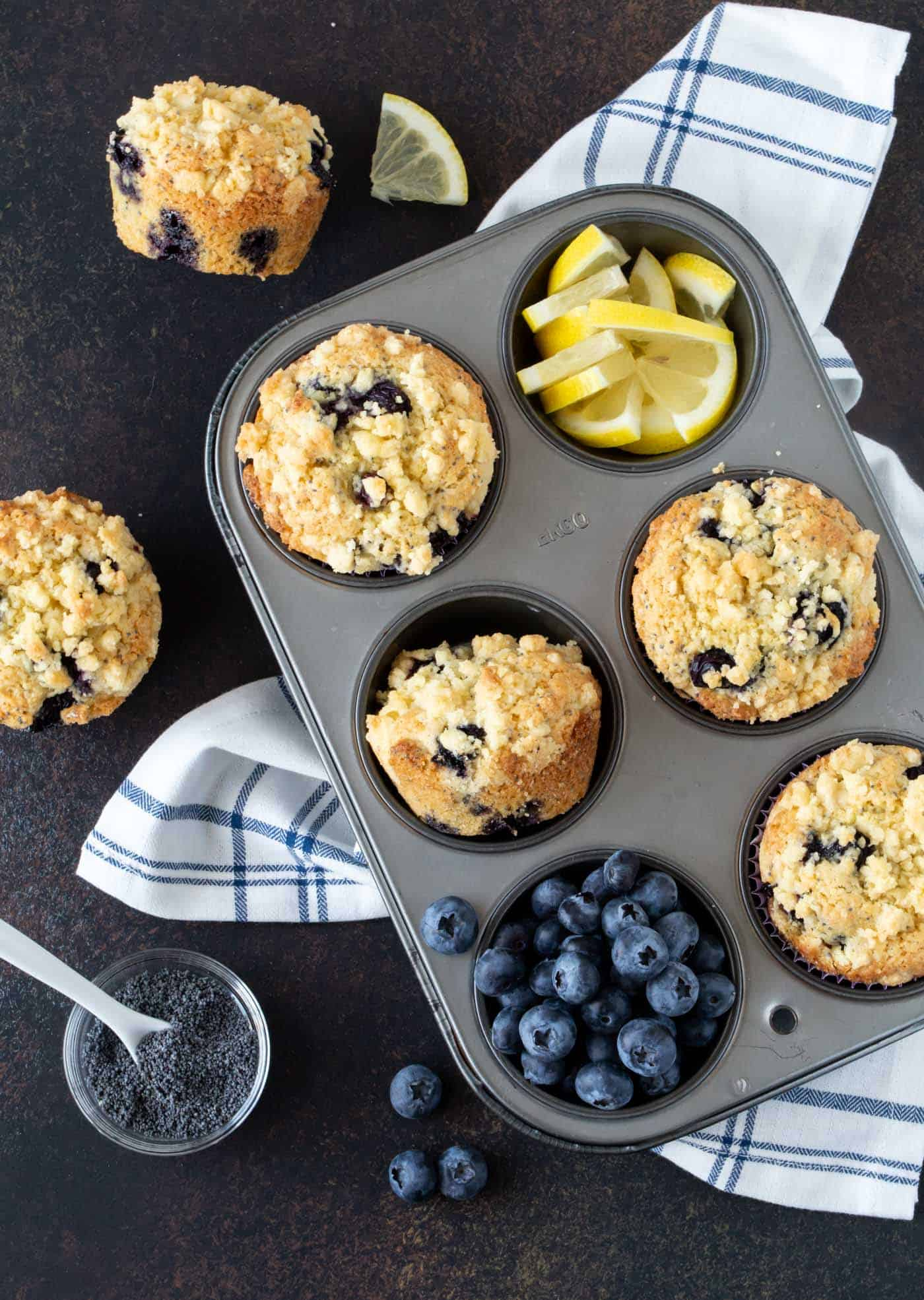 Muffin tin filled with four Blueberry Lemon Poppy Seed Muffins. Garnished with fresh blueberries and lemon slices.