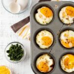 Cheesy Spinach and Ham Egg Cups baked in a muffin tin on a white wooden board. Surrounded by chopped spinach, eggs, shredded cheddar cheese and salt and pepper shakers.