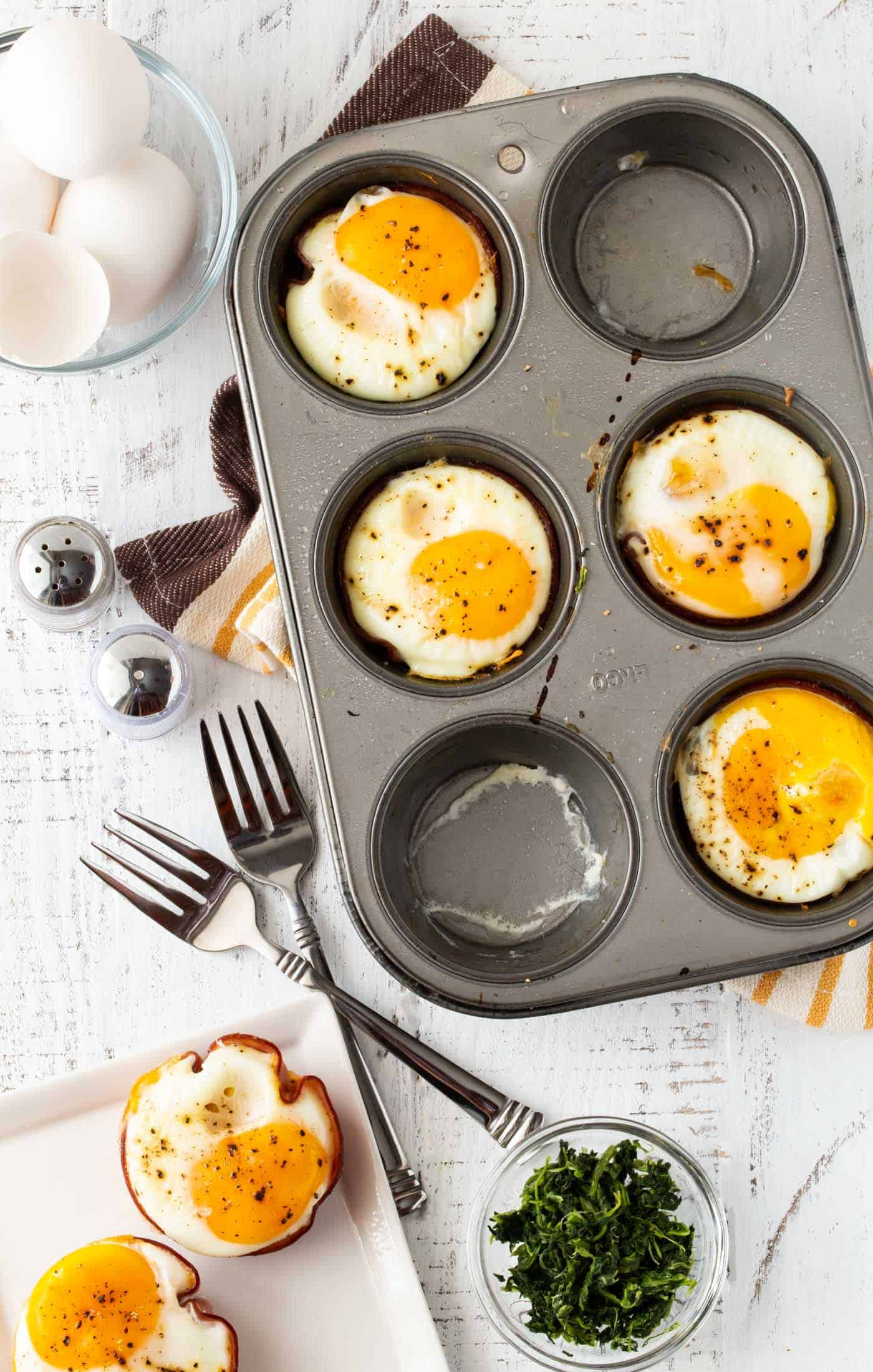 Muffin tin full of Cheesy Spinach and Ham Egg Cups. Surrounded by baked egg cups on a white plate, forks, salt and pepper shakers.