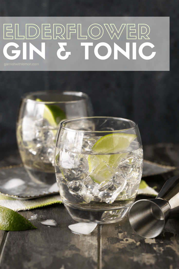Two lowball glasses of elderflower gin and tonic cocktails on a dark wood board. Garnished with ice and lime wedges